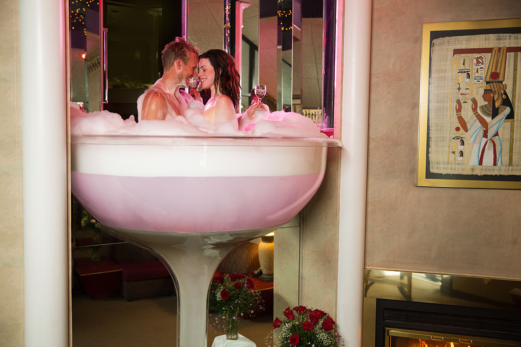 A couple enjoying a bubble bath in a champagne glass shaped tub: Poconos Romantic Getaway