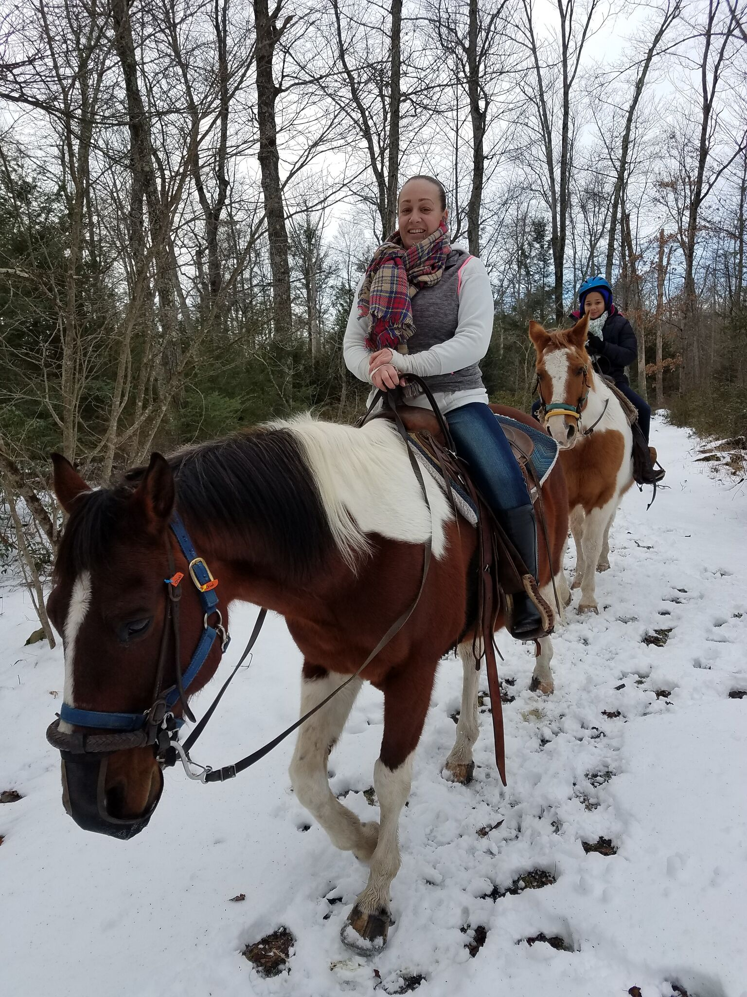 A woman horseback riding in the snow.